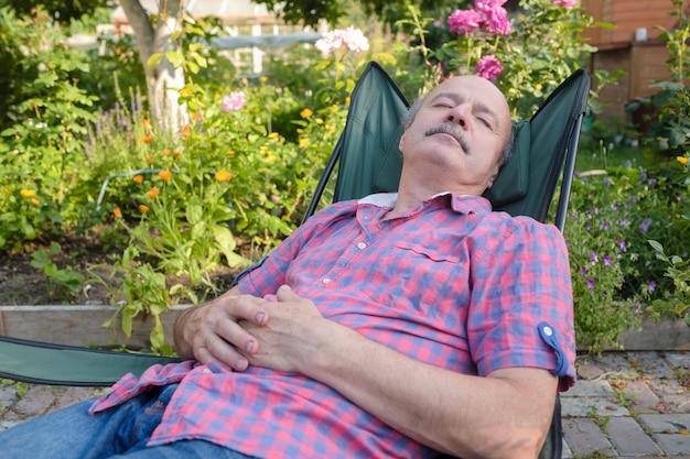 夏の屋外フラワーガーデンで眠っている椅子に戻って傾いて座っている男