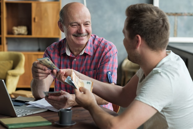 年長の父親は彼の大人の息子にお金を貸します