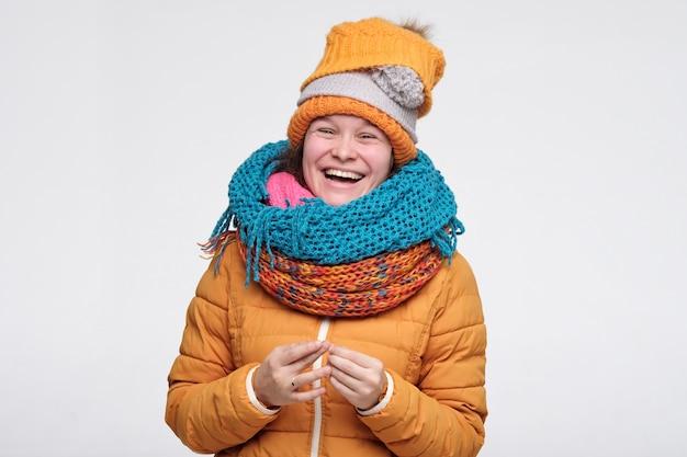 Женщина в шарфах и шляпе весело смеется