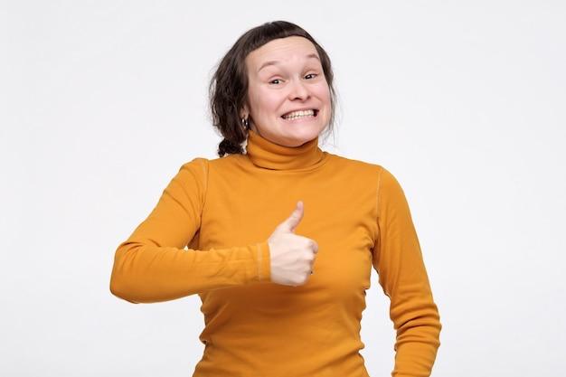 あなたの選択を承認する親指を示す幸せな興奮した女性