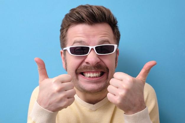 レトロな口ひげと親指をあきらめてサングラスを持つ男