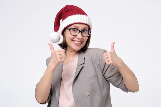赤いサンタ帽子とメガネの女性があなたの選択を承認する親指を表示
