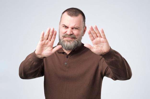 ひげを持つ成熟した男は拒否ジェスチャーを示し、あなたと話したくない