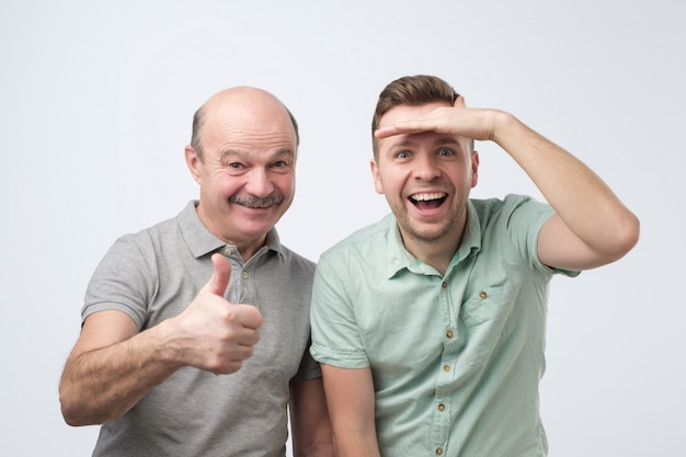 興奮した白人男性の父と息子は驚いています