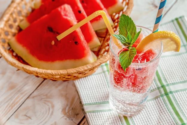 スイカのスライス、ミント、木製の背景にレモンと新鮮な夏の冷たい飲み物