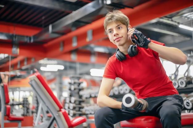 Молодой человек в фитнес-клубе с гантелями в руках разговаривает по телефону, современный спортивный образ жизни