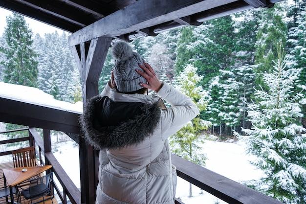 Молодая девушка стоит на террасе в белой куртке и шапке с видом на зимний лес