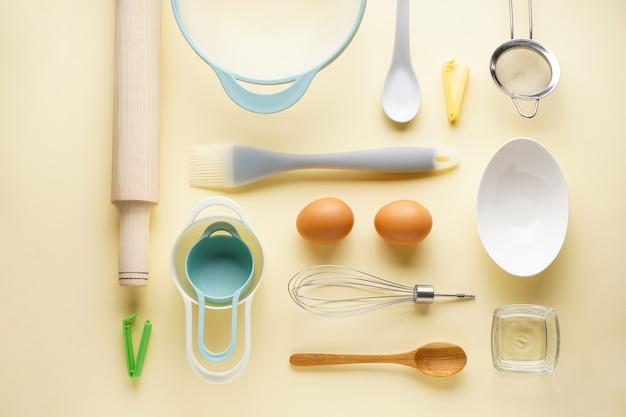 黄色の背景、上面にさまざまな台所用品。