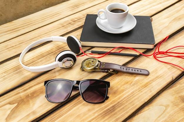 黒のメモ帳、ヘッドフォン、木製の背景のコーヒー。