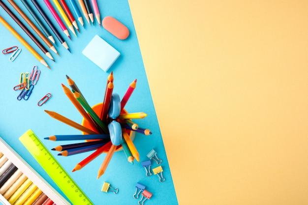 青と黄色のテクスチャ紙の背景に学校のコンセプトに戻る。