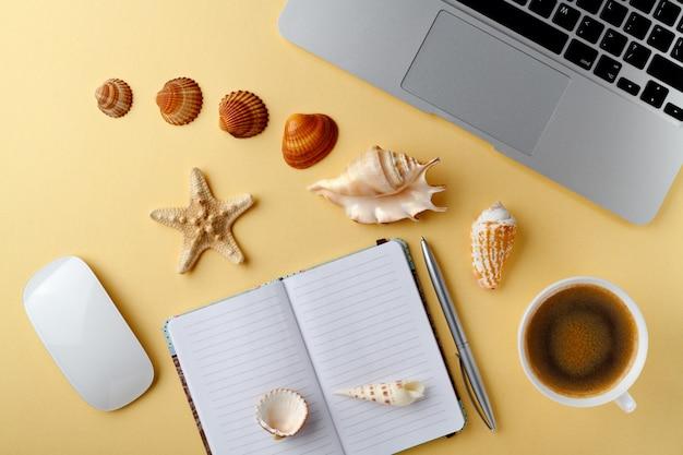 トップビューの黄色のテーブルは、コーヒーマウスペンシェルのノートブックカップを開きます。旅行休暇の概念。熱帯のビーチでの休暇を夢見ています。