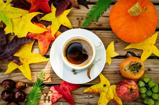 柿、リンゴ、ブドウ、カボチャ、栗、コーヒーのマグカップを黄色、赤、茶色の落ち葉と素朴な木製のテーブルの上に平らに並べたもの