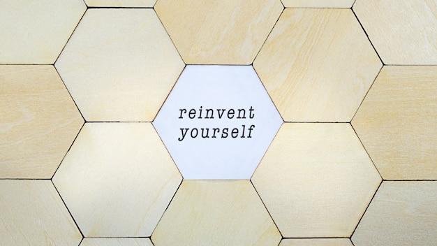 パズルから欠落している木製の六角形、単語が個人の成長と自己発見の概念図で自分自身を再発明することを明らかにする