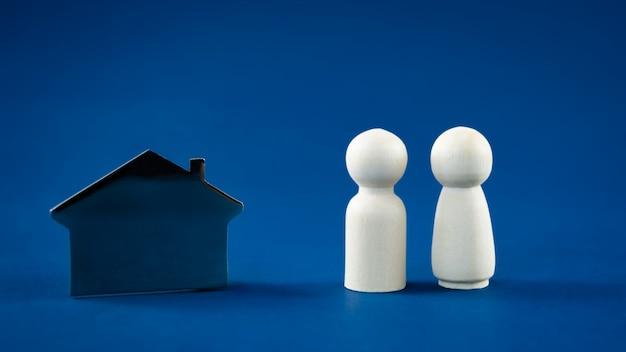 Модель металлического дома с мужской и женской фигуркой в концептуальном изображении покупки или строительства нового дома