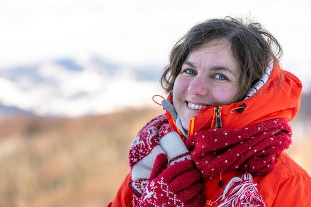 Девушка в норвежской одежде улыбается на фоне зимних горных вершин