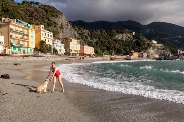 Красивая улыбка девушки на пляже курорта чинкве тере с собакой
