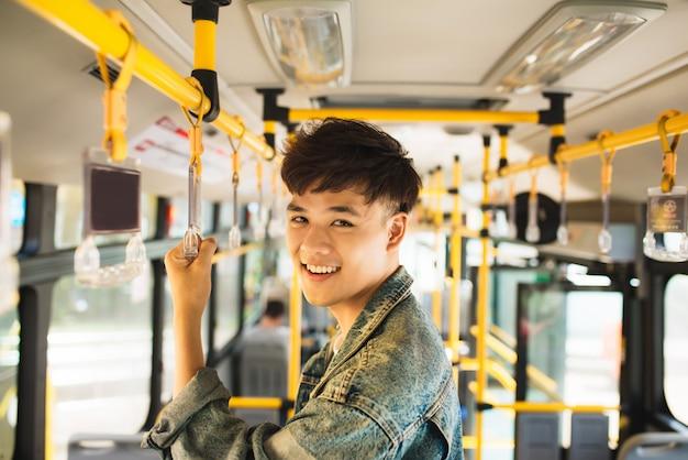 Человек, пользующийся общественным транспортом, стоит в автобусе