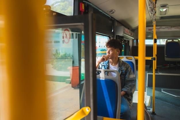 Человек сидит в городском автобусе, слушает музыку и смотрит в окно