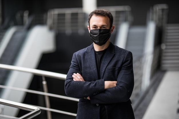 医療マスクのビジネスマンは、オープンスペースのオフィスで働いています。スーツを着た男性のマネージャーがコロナウイルスの流行中に安全対策に従っている