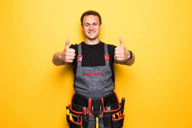Счастливый красивый молодой работник улыбается и недурно, парень носить спецодежду и поясное оборудование
