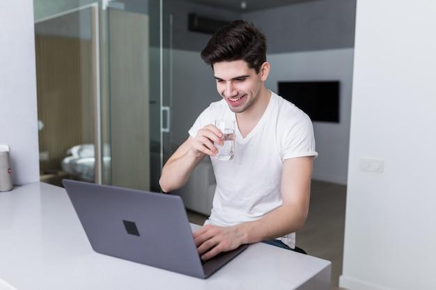 ハンサムな若い男が自宅のキッチンでノートパソコンでの作業中に水を飲む