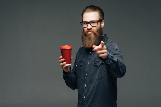 スタイリッシュな髪のひげと深刻な顔に口ひげを生やしたハンサムなひげを生やした男がカメラを保持しているカップまたは灰色の空間でお茶やコーヒーを飲むマグカップを指して
