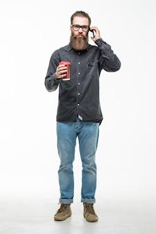 スタイリッシュな髪のひげと口ひげのカップまたはマグカップホワイトスペースでお茶やコーヒーを飲んで携帯電話で話しているハンサムなひげを生やした男
