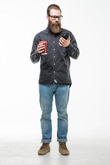 スタイリッシュな髪のひげと口ひげを持つハンサムなひげを生やした男は、携帯電話を保持しているカップまたはマグカップホワイトスペースでお茶やコーヒーを飲む
