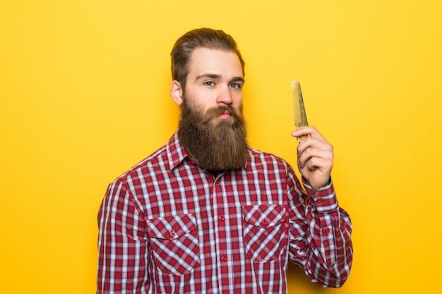 Счастливый молодой битник человек расчесывать его борода и усы на желтом пространстве.