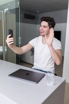 こんにちは私の新しい家から。新しい青いデニムシャツジーンズで格好良い男の摩耗電話で見る友人と話すテーブル屋内白い明るい光アパート