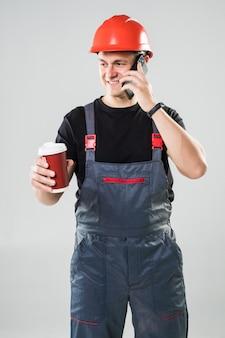 Улыбающийся строитель в каске пьет кофе, чтобы поговорить по телефону