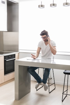 Сконцентрированный молодой бизнесмен работая внутри помещения пишущ примечания говоря мобильным телефоном дома