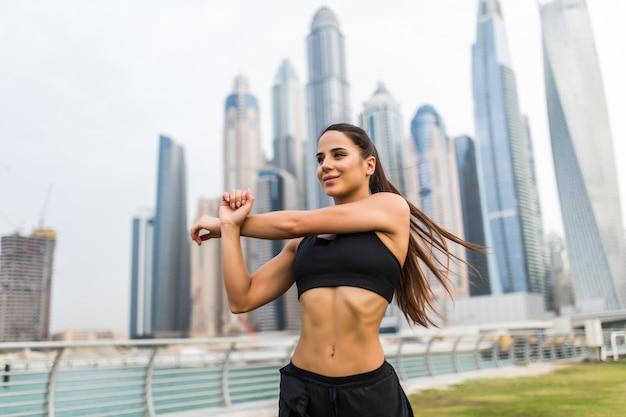 Молодая женщина фитнеса делает согревающие руки упражнения перед бегом против пространства небоскребов