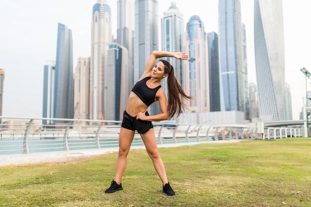 Девушка привлекательной пригонки молодая делая упражнения на растяжку стоя на космосе небоскребов