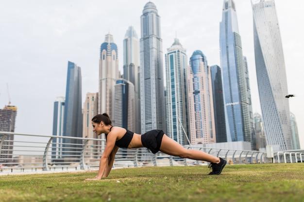 Молодая женщина фитнеса делает упражнения доски перед небоскребами