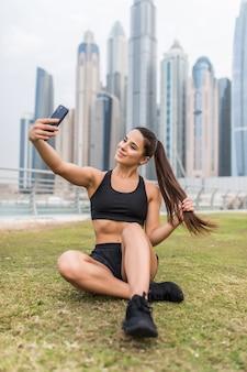 Молодая спортивная женщина делает селфи на телефоне сидя и отдыхая на пространстве небоскребов
