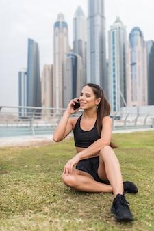 Молодая спортивная женщина разговаривает по телефону сидя и отдыхая на небоскребах