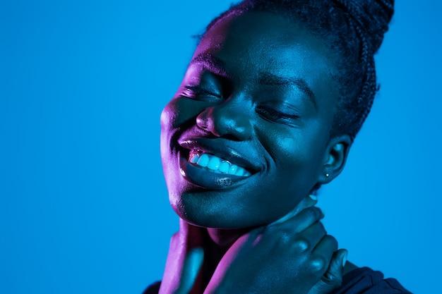 ネオン空間でポーズかなりアフリカの若い女性の肖像画。スキンケアのコンセプトです。
