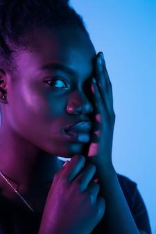 ファッショナブルなネオンの光空間で若いエレガントなアフリカ系アメリカ人女性。