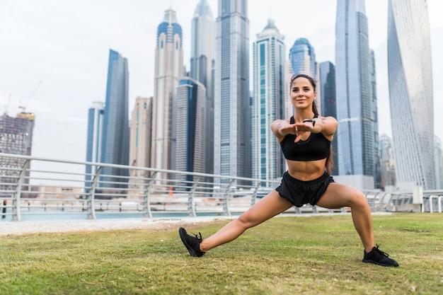 Молодая женщина фитнес, растяжение ноги разминки перед тренировкой на пространстве небоскребов