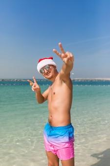 Молодой красавец в шляпу санта и солнцезащитные очки с жестом мира, стоя в морской воде