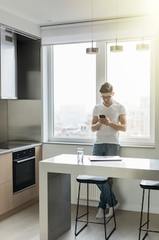 ハンサムな若い男が台所で彼のスマートフォンでテキストメッセージ