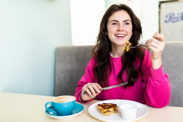 魅力的な幸せな若い女性に座って、カフェでデザートを食べる