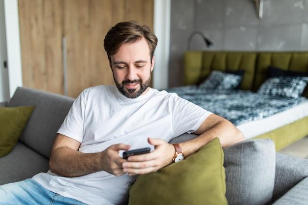 携帯電話を使用してチャットのタイピングメッセージを笑顔で自宅のソファのリビングルームに座っている千年の男。
