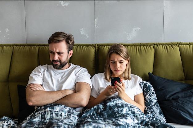 自宅のベッドに横たわっている間携帯電話についての議論を持つ混乱している若いカップル