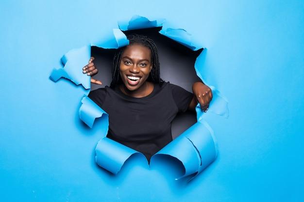 青い紙の穴からポーズをとって若いアフロアメリカンの女性