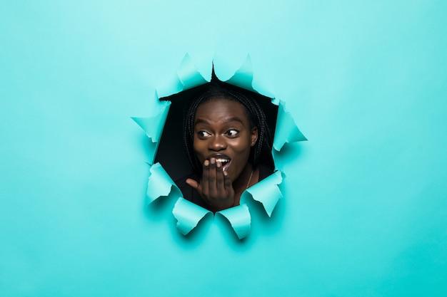 黄色い紙の穴からポーズをとって若いアフロアメリカンの女性