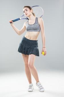 孤立した白い壁の上の若いテニスプレーヤーの女性のフルレングス