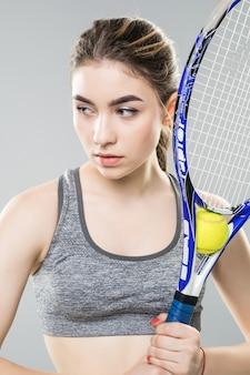 分離された彼女の顔にテニスラケットを持つ若い女性。中立的な顔と自信に満ちた表情。クローズアップショット。