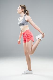 立っていると足を伸ばして若いフィットネス女性の側面の肖像